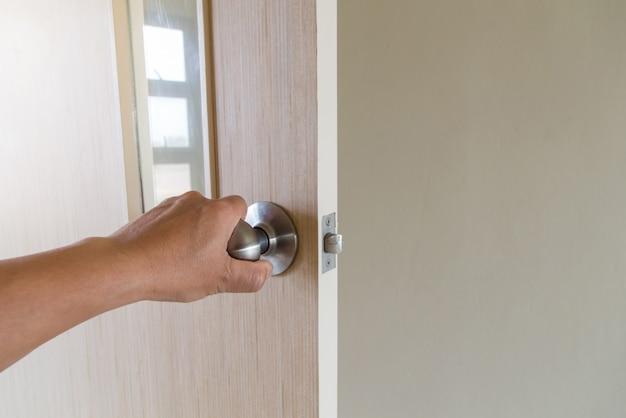 Die hand von menschen öffnet die tür nach innen, die außentür öffnet sich in die haustür