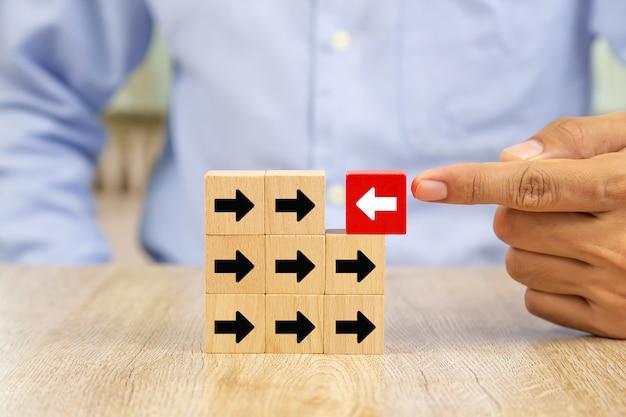 Die hand wählte das weiße pfeilsymbol auf dem holzblock aus, das die entgegengesetzte richtung wie der schwarze pfeil hat.