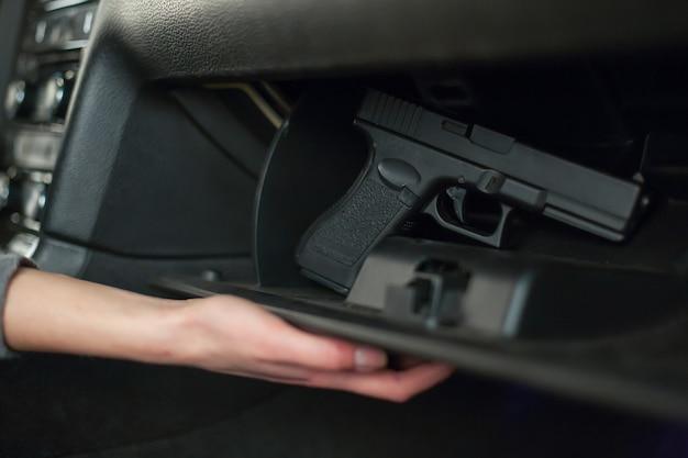 Die hand zieht eine pistole aus dem handschuhfach.