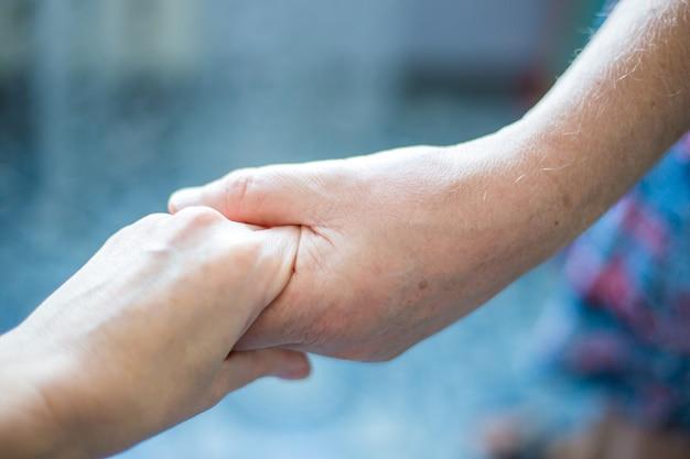 Die handfläche einer frau liegt in der hand eines mannes. häusliche gewalt