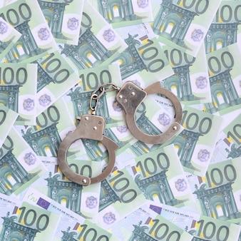 Die handschellen der polizei liegen auf einer reihe grüner währungsbezeichnungen von 100 euro.