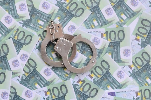 Die handschellen der polizei liegen auf einer reihe grüner währungsbezeichnungen von 100 euro