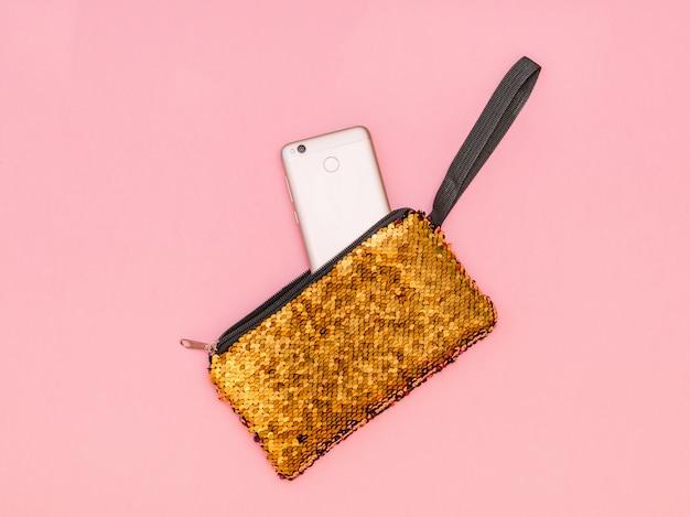 Die handtasche der frauen mit einem haftenden telefon der goldfarbe auf einer rosa tabelle. pastellfarbe. flach liegen.