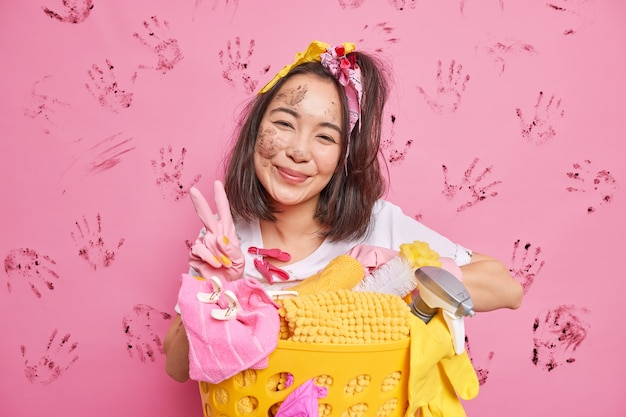 Die hart arbeitende, zufriedene junge asiatische hausfrau mit schmutzigem gesicht trägt gummihandschuhe zum waschen schräger kopfposen in der nähe des wäschekorbs macht eine friedensgeste einzeln über rosafarbener wand mit handabdrücken
