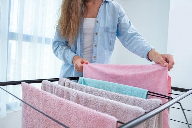 Die hausfrau hängt gewaschene kleidung an den wäschetrockner