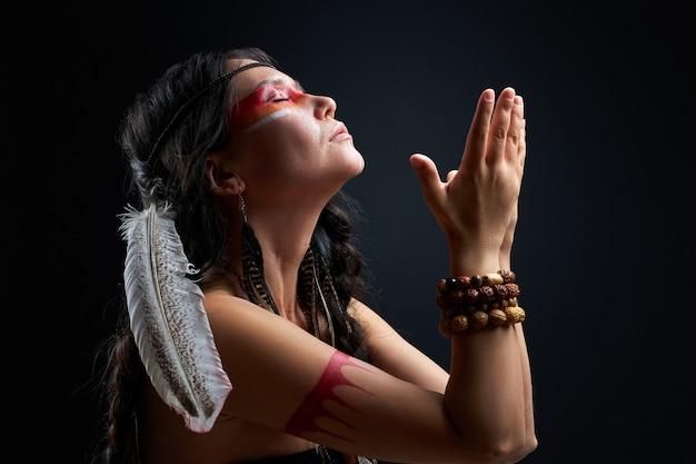 Die heidnische frau ist eine schamanin an einer schwarzen wand