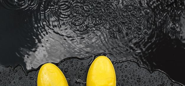 Die hellen gelben gummistiefel der frauen stehen unter regentropfen auf schwarzem
