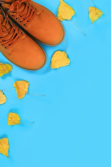 Die herbststiefel der orange braunmänner auf einem blauen pastellhintergrund. draufsicht, kopie, raum.