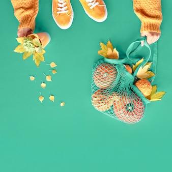 Die herbstwohnung lag auf lebhaftem grünem hintergrund von biscay. orange kürbisse im netzbeutel, gelbe ahornblätter, weibliche hände im orangefarbenen pullover und ein paar segeltuchschuhe.