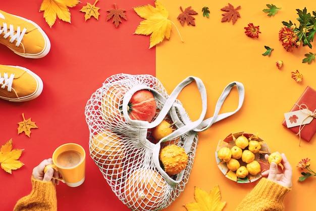 Die herbstwohnung lag in grün und orange mit kürbissen in einer saitentasche, turnschuhen und weiblichen händen mit einer tasse kaffee und gelben früchten