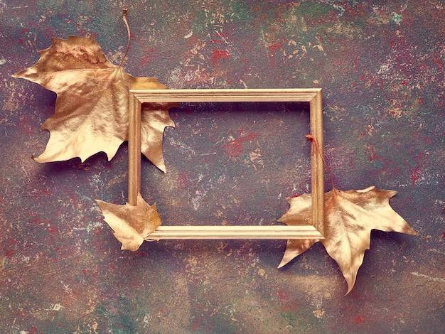 Die herbstwohnung lag mit bergahornblättern, die goldfarben bemalt waren, und einem kopierraum in einem goldenen rahmen auf einer dunkel strukturierten leinwand