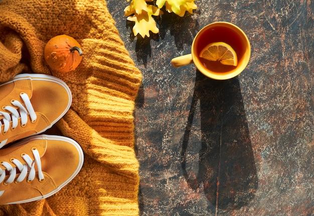 Die herbstwohnung lag mit gelbem pullover, turnschuhen, dekorativen kürbissen, eichenblättern und einer tasse tee mit zitrone im dunkeln
