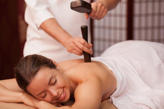 Die herrliche frau, die mit ihren augen lächelt, schloss das genießen der traditionellen thailändischen hammermassage in der badekurortmitte. schöne glückliche frau, die tok sen massage vom berufsmasseur empfängt. reisen, gesundheitskonform