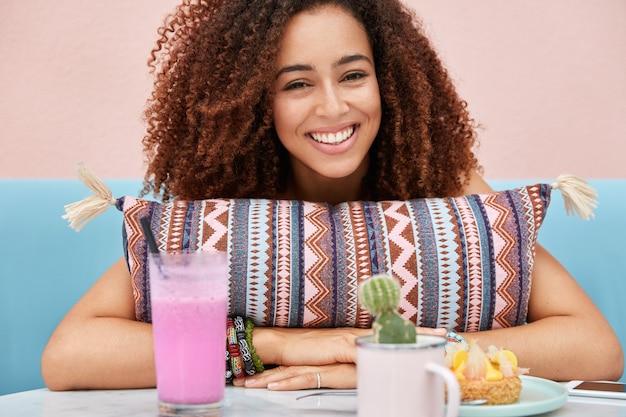Die horizontale aufnahme einer erfreuten attraktiven lockigen afroamerikanischen frau verbringt ihre freizeit in der cafeteria und hört glücklich ihrem freund zu, der lustige geschichten erzählt