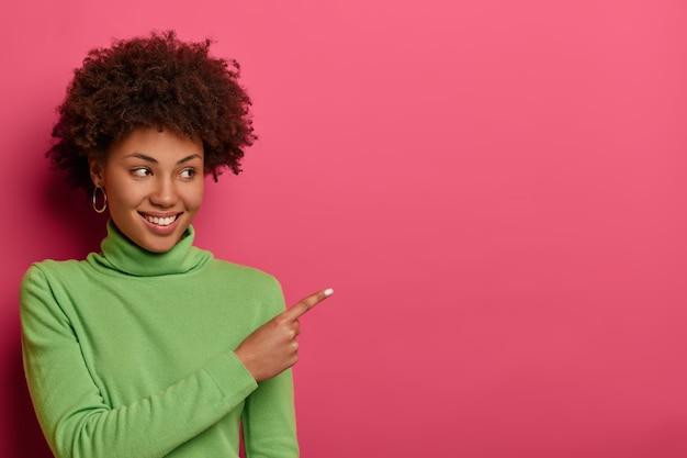 Die horizontale aufnahme einer lächelnden frau mit lockigen haaren zeigt an, dass platz frei ist, platz für ihre werbung zeigt, die aufmerksamkeit auf den verkauf lenkt, einen grünen rollkragenpullover trägt, der auf einer leuchtend rosa wand isoliert ist