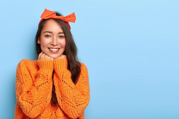 Die horizontale aufnahme einer zufriedenen schönen asiatischen dame berührt das kinn mit beiden händen, lächelt angenehm, hat langes dunkles haar und trägt einen orangefarbenen pullover