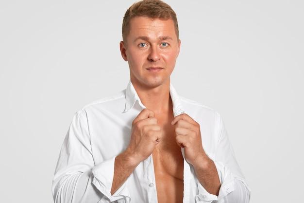 Die horizontale aufnahme eines ernsthaften attraktiven mannes trägt ein weißes hemd, zeigt seinen perfekten körper, hält sich fit, ist profisportler, hat eine gesunde haut und ist auf weiß isoliert. menschen- und sportkonzept