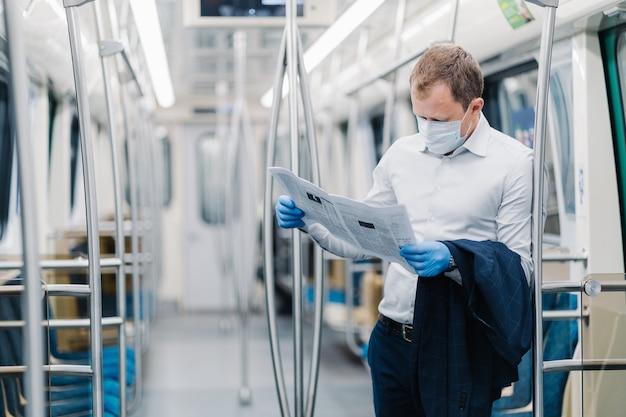 Die horizontale aufnahme eines erwachsenen mannes trägt formelle kleidung, eine medizinische schutzmaske und handschuhe, liest die presse, findet nachrichten während des virusausbruchs heraus und pendelt zur arbeit im öffentlichen verkehr. coronavirus (covid-19