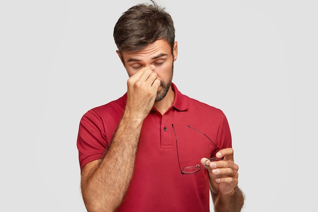 Die horizontale aufnahme eines überarbeiteten, gutaussehenden mannes hält die hand auf der nase, nimmt die brille ab, fühlt nach der arbeit am computer augenschmerzen, möchte schlafen, trägt ein lässiges rotes t-shirt, das über der weißen wand isoliert ist