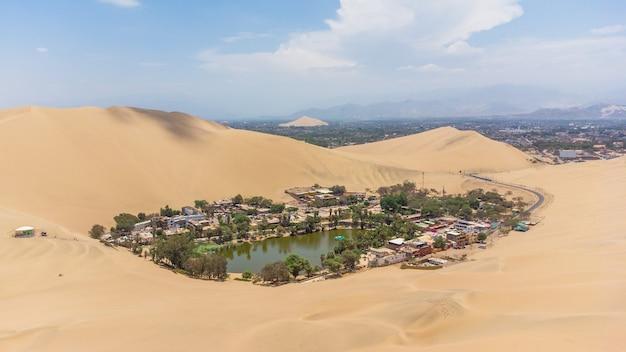 Die huacachina-oase ist eine natürliche oase mitten in der wüste, die sich in der stadt ica in peru befindet