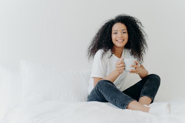 Die hübsche afroamerikanerfrau, die im bett zu hause stillsteht, trinkt heißen tee am morgen genießt inländische atmosphäre