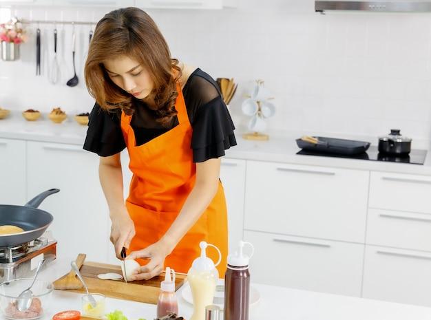 Die hübsche asiatische mutter trägt eine orangefarbene küchenschürze und achtet darauf, zu lernen, wie man zwiebeln zu hause in stücke schneidet, während sie von der kochschule erzogen wurde, um gesundes essen für das kind ihrer familie zuzubereiten.