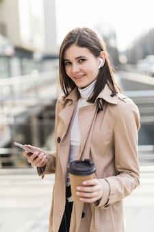 Die hübsche dame trinkt kaffee und liest draußen auf ihrem handy nachrichten