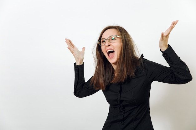 Die hübsche europäische junge wütende braunhaarige frau mit brille für die sicht mit gesunder, sauberer haut, gekleidet in ein dunkelschwarzes hemd, schreit und fluchend, auf weißem hintergrund. emotionen-konzept.