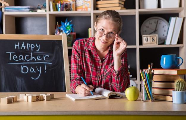 Die hübsche frau des lehrers genießt den bildungsprozess im klassenzimmer. lehrertag. (weicher fokus auf mädchen)
