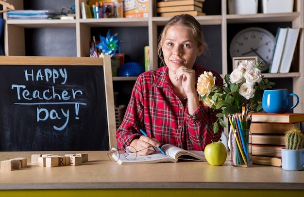 Die hübsche frau des lehrers genießt den bildungsprozess im klassenzimmer. lehrertag.