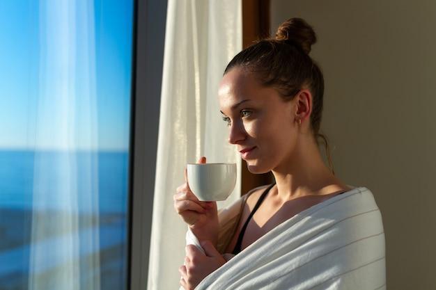 Die hübsche frau, die in eine decke eingewickelt wird, steht nahes fenster und genießt kaffee des ersten morgens auf sonnenschein. ein frühes aufwachen und der beginn eines neuen tages