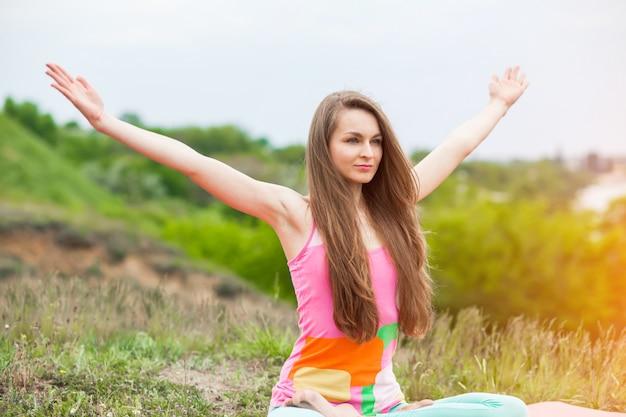 Die hübsche frau, die yoga tut, trainiert auf naturlandschaft