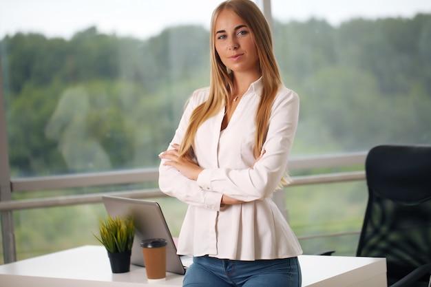 Die hübsche junge geschäftsfrau, die am arbeitsplatz steht