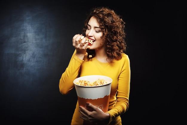 Die hungrige frau isst eine handvoll popcorn, während sie auf den film wartet