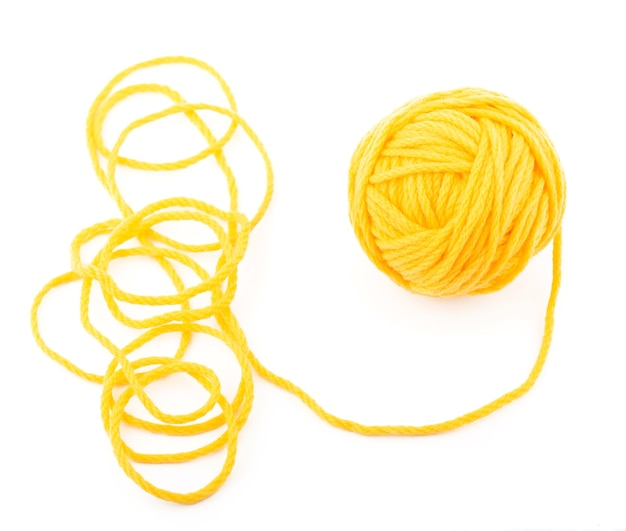 Die idee ist ein wirrwarr. gelber wollknäuel auf weißem tisch