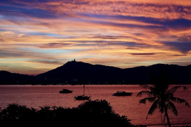 Die idyllische szene des sonnenuntergangs am tropischen strand und an der insel in thailand.
