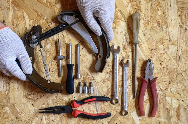Die in den behandschuhten händen der männer zerlegte autotrommelbremse und ein satz verschiedener reparaturhandwerkzeuge oder das werkzeugset des automechanikers auf einem blatt osb-sperrholz-hintergrund. flach liegen, draufsicht