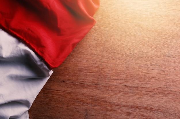 Die indonesische flagge ist rot und weiß mit einem holztischhintergrund