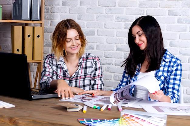 Die innenarchitekten der jungen freiberufler, die arbeiten, entwickeln neues wohnungsprojekt im designstudio. weibliche sitzung mit zwei frauenmädchen mit treffenschreibtisch mit stift herauf skizzenzeichnungen und entwürfe des neuen projekts