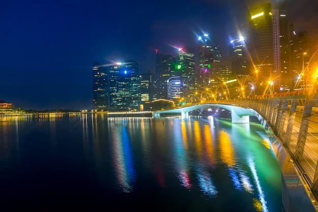 Die innenstadt von singapur liegt in einem leichten nebel. nacht marina bay. fußgängerzone esplanade bridge, schlafender merlion und wolkenkratzer