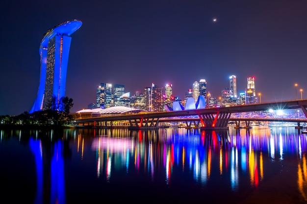 Die innenstadt von singapur mit sand hotel, wolkenkratzern und zwei brücken. mond und schöne nachtbeleuchtung