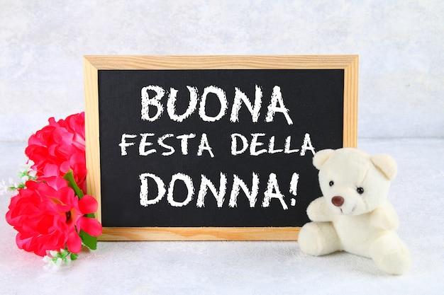 Die inschrift auf der tafel auf italienisch: der tag der glücklichen frau. rosa blumen und teddybär.