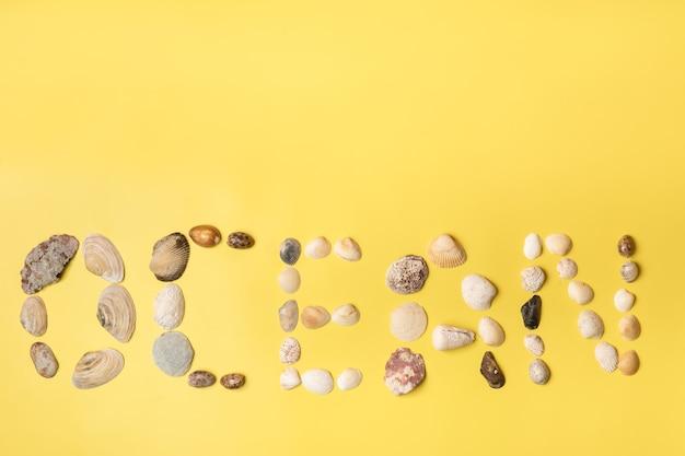 Die inschrift des wortes ozean aus muscheln auf gelbem hintergrund. reisekonzept