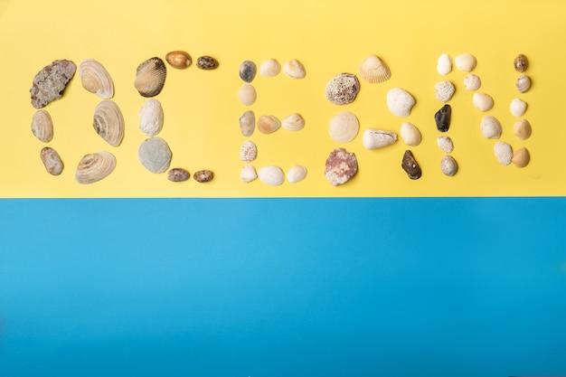 Die inschrift des wortes ozean besteht aus muscheln auf gelb-blauem hintergrund. reisekonzept