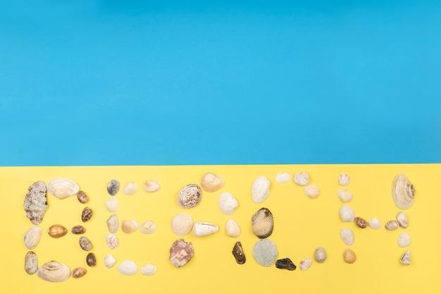 Die inschrift des wortes strand besteht aus muscheln auf gelb-blauem hintergrund. reisekonzept