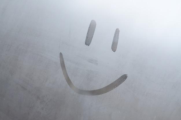 Die inschrift lächelt auf dem beschlagenen verschwitzten glas. abstraktes hintergrundbild
