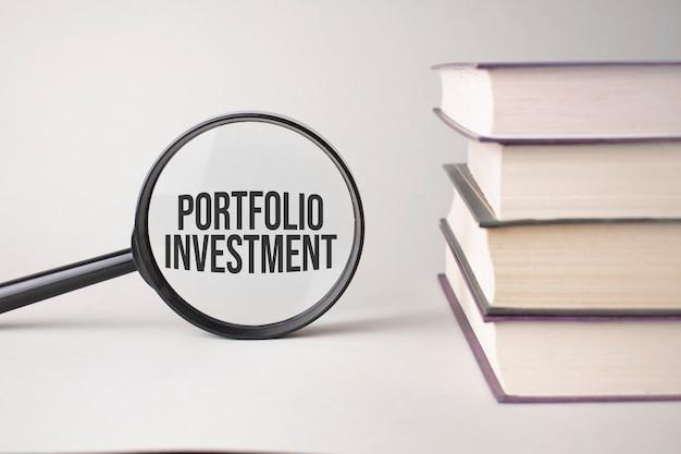Die inschrift portfolio-investition ist geschrieben und die bücher. content lettering ist für geschäftsinhalte und marketing unerlässlich.