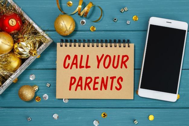 Die inschrift ruf deine eltern auf dem notizbuch mit goldener weihnachtsdekoration und smartphone an