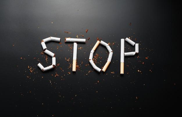 Die inschrift stop von zigaretten. aufhören zu rauchen. das konzept des rauchens tötet. motivationsschild zur raucherentwöhnung, ungesunde gewohnheit.