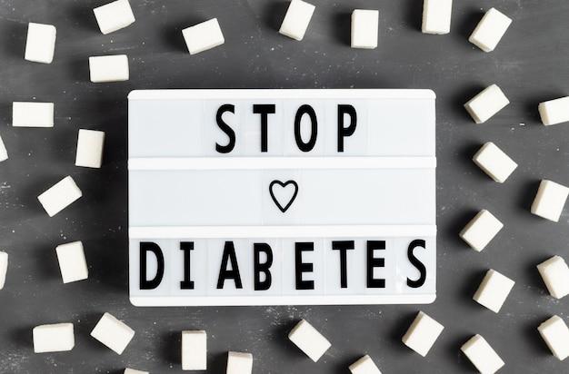 Die inschrift stoppt diabetes auf einer weißen tafel auf grauem hintergrund